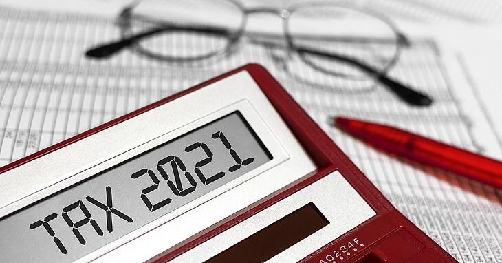 a pair of glasses, a red pen, and a red calculator that reads tax 2021