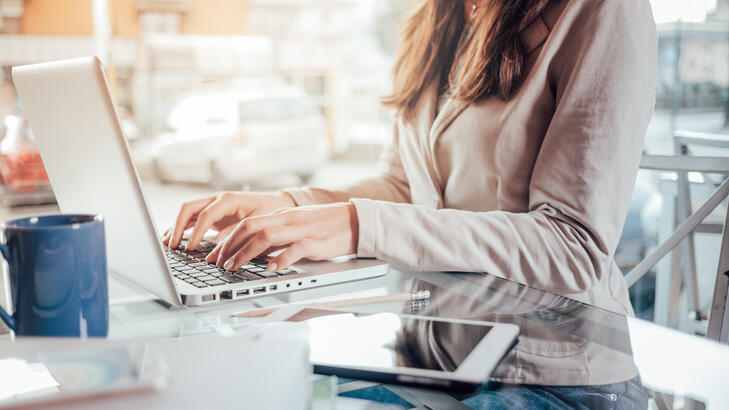 businesswoman typing on a laptop managing expenses