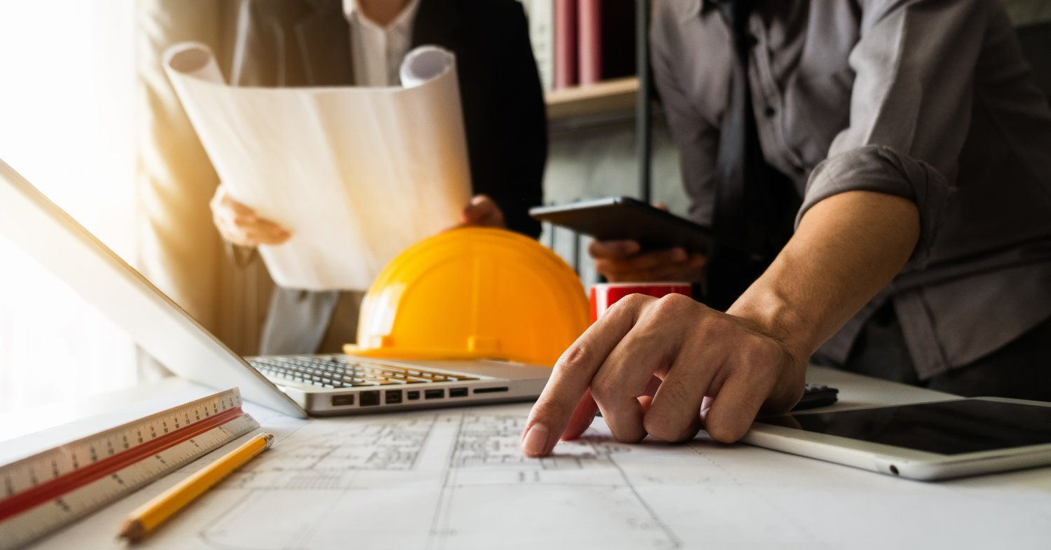 finance leader pointing at construction blueprint