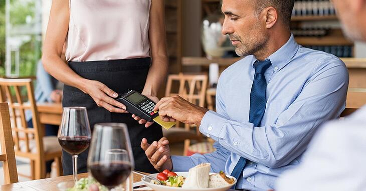 businessman in a blue shirt and tie paying for his meal with a credit card