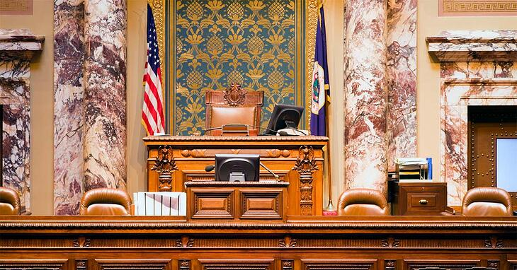 the judge's bench in the Minnesota judicial courthouse sitting between two marble columns and American flags